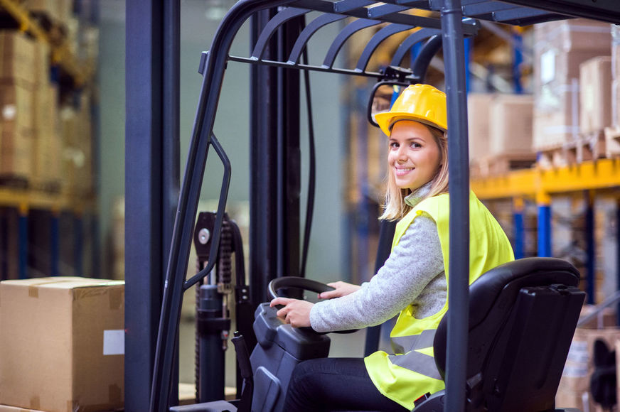 Woman warehouse worker with forklift