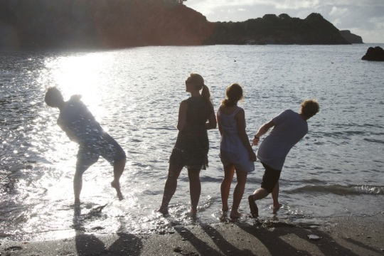 Friends skimming stones at hidden Exmoor beach by James Walker for Visit Exmoor and Visit Somerset